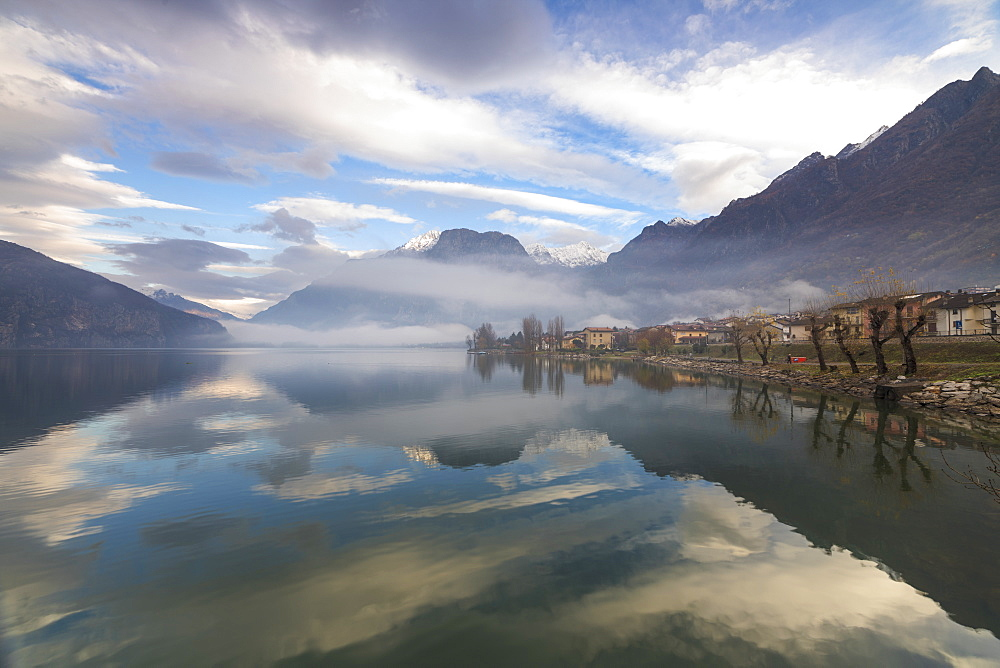 Mountains and village are reflected in Lake Mezzola at dawn shrouded by mist, Verceia, Chiavenna Valley, Lombardy, Italy, Europe