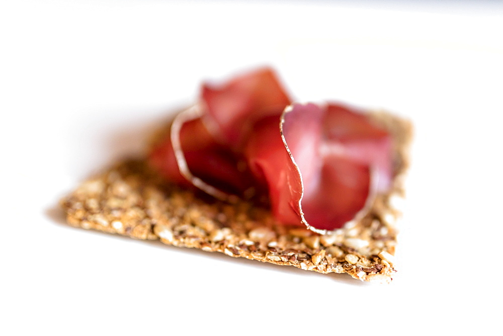 Close up of Bresaola, the typical raw beef cured by salting and air-drying, on white background, Valtellina, Lombardy, Italy, Europe