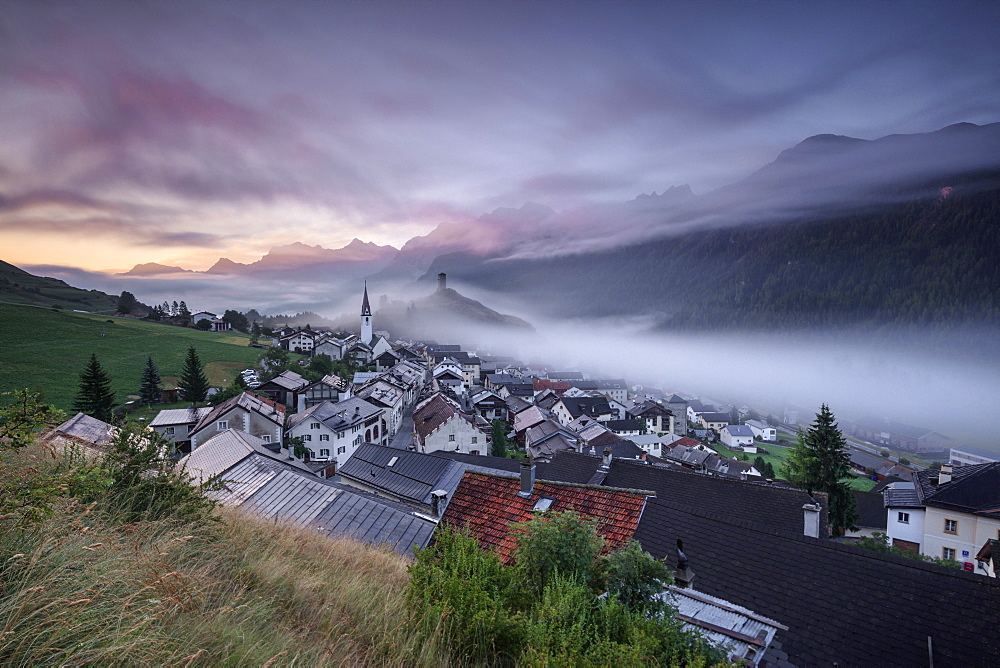 Pink clouds and mist on the village of Ardez at dawn, canton of Graubünden, district of Inn, lower Engadine, Switzerland, Europe