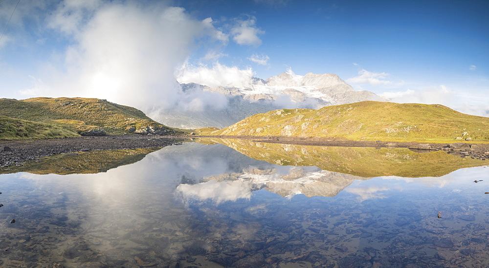 Panoramic of mountain peaks reflected in lake, Bernina Pass, Poschiavo Valley, canton of Graubünden, Engadine, Switzerland