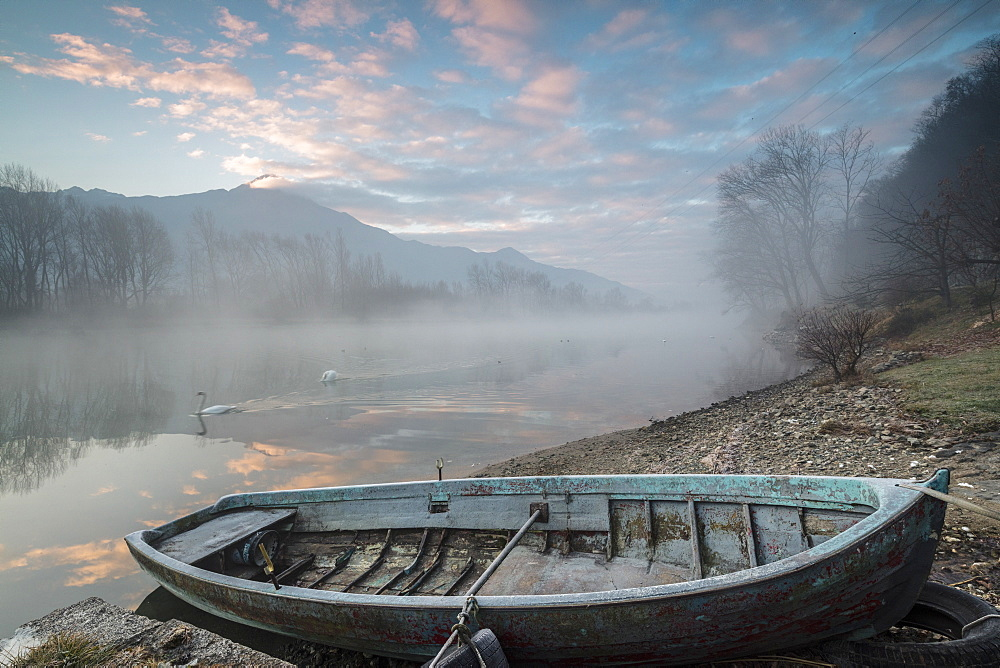 Wood boat on the shore of river Mera at sunrise, Sorico, Como province, Lower Valtellina, Lombardy, Italy