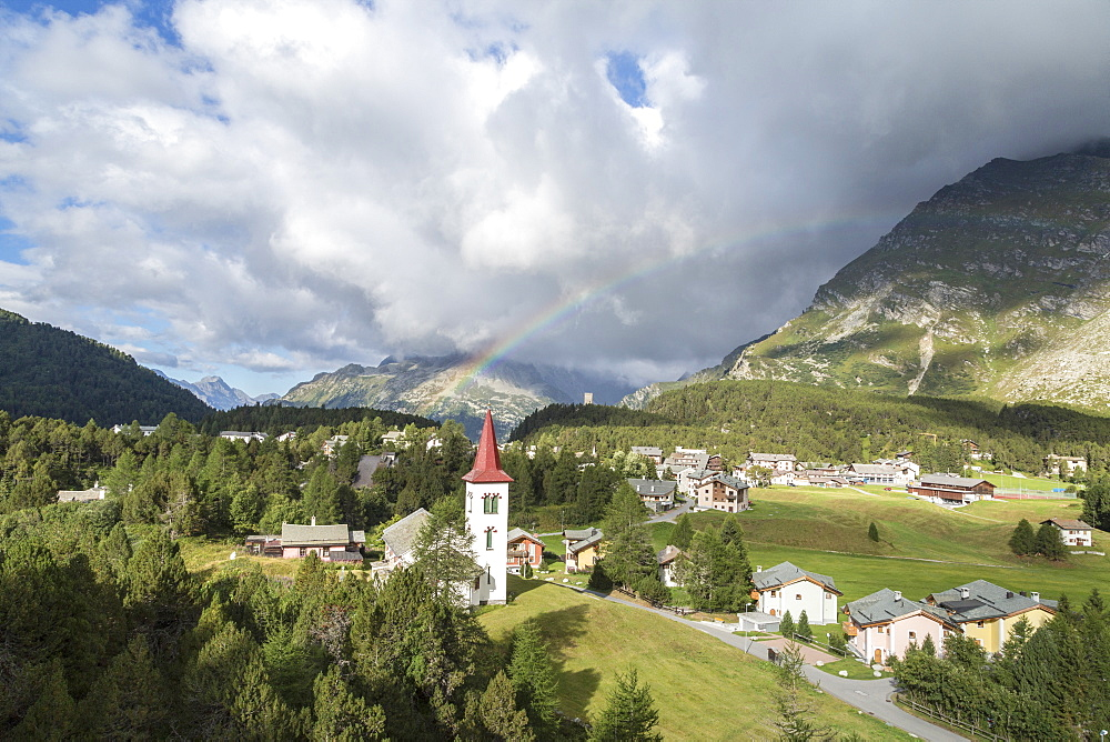 Rainbow over Chiesa Bianca and the village of Maloja, Bregaglia Valley, Engadine, Canton of Graubunden (Grisons), Switzerland, Europe