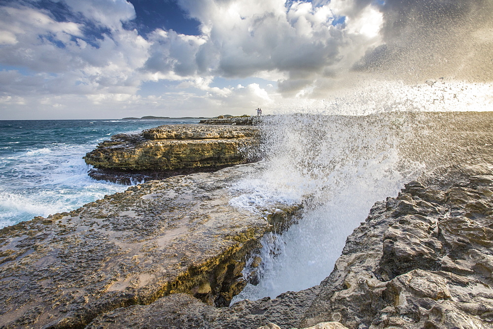 A wave created by the strong wind squirts water over Devils Bridge, a coral bridge created by wind and the power of sea, Antigua, Leeward Islands, West Indies, Caribbean, Central America