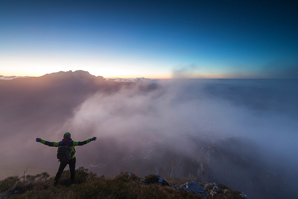 Hiker on top of Monte Coltignone at dawn, province of Lecco, Lombardy, Italy - 1179-2992