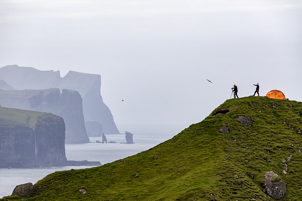 Hikers and tent on cliffs, Kalsoy Island, Faroe Islands, Denmark, Europe