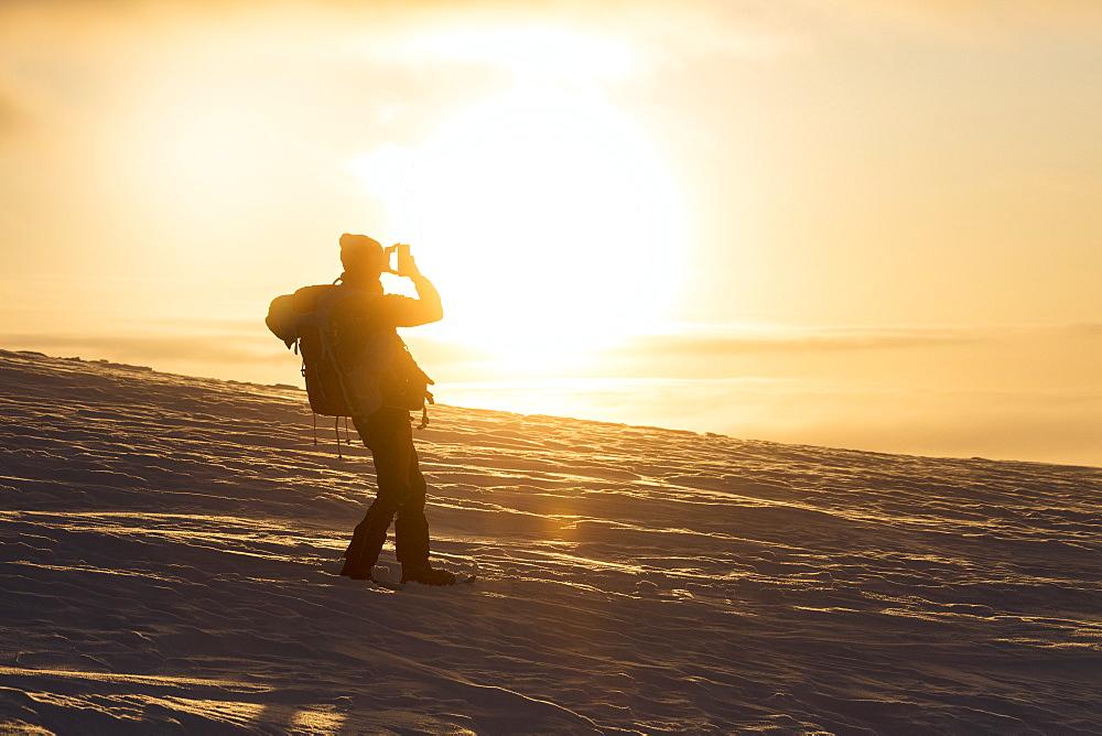 Photographer at sunset, Pallas-Yllastunturi National Park, Muonio, Lapland, Finland, Europe