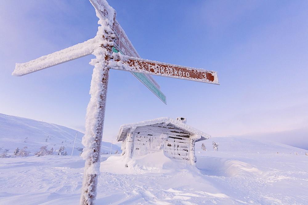 Frozen signage and wood hut, Pallas-Yllastunturi National Park, Muonio, Lapland, Finland, Europe