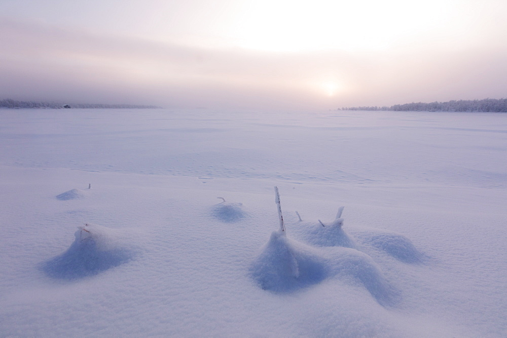 Misty sunrise on the snowy landscape, Muonio, Lapland, Finland