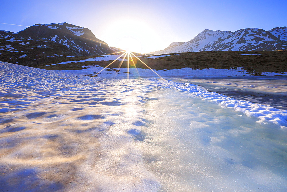 Sunburst on Lake Andossi during thaw, Chiavenna Valley, Spluga Valley, Sondrio province, Valtellina, Lombardy, Italy, Europe