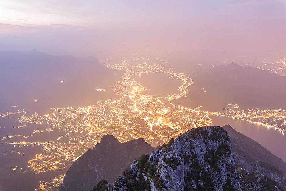 Illuminated city of Lecco seen from Monte Coltignone at dawn, Lombardy, Italy