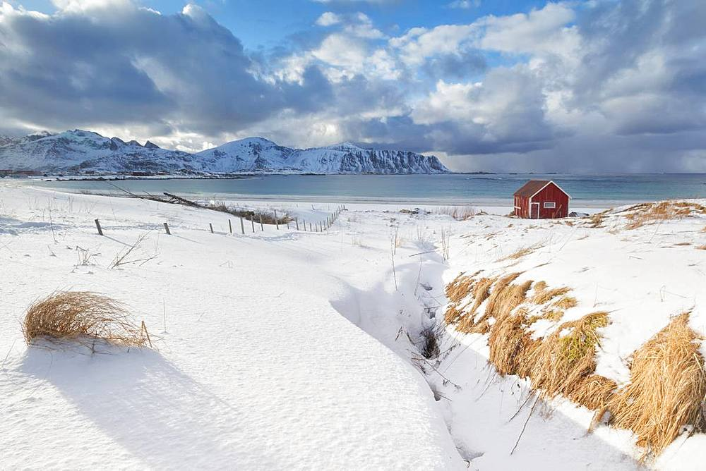 Wood cabin on sand beach covered with snow, Ramberg, Flakstad municipality, Lofoten Islands, Norway