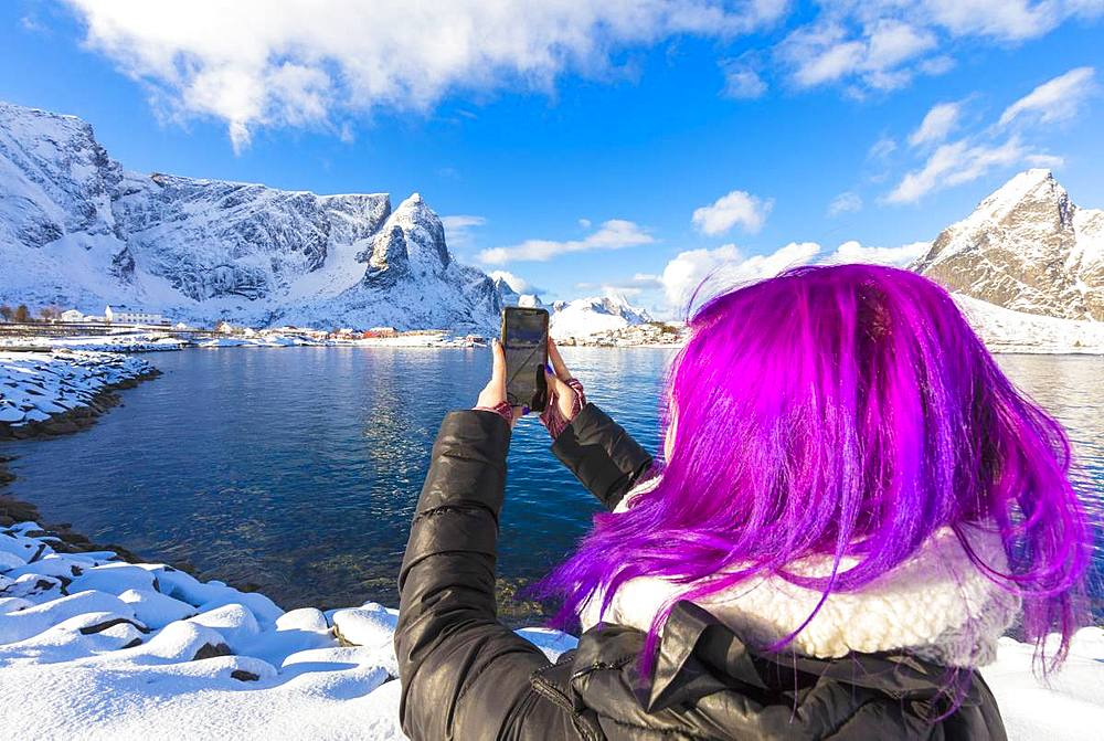 Woman with fuchsia hair taking photo with smartphone, Reine Bay, Lofoten Islands, Nordland, Norway, Europe - 1179-3390