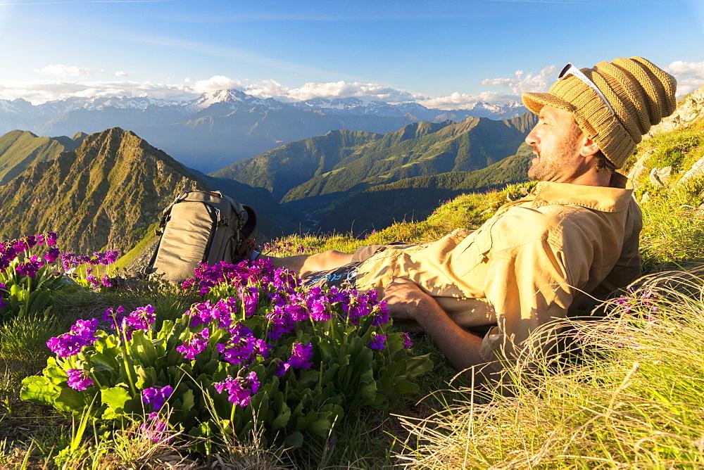 Man lying down on top of Monte Azzarini looks to Monte Disgrazia and Monte Pedena, Albaredo Valley, Orobie Alps, Lombardy, Italy, Europe