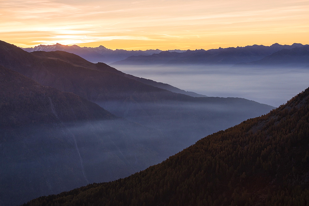 Silhouettes of the Orobie Alps in the mist of autumnal sunset, Valmalenco, Valtellina, Lombardy, Italy, Europe