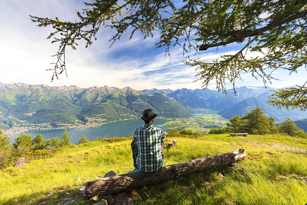 Man sitting on tree trunk looks towards Lake Como and Alto Lario, Monte Legnoncino, Lecco province, Lombardy, Italy, Europe