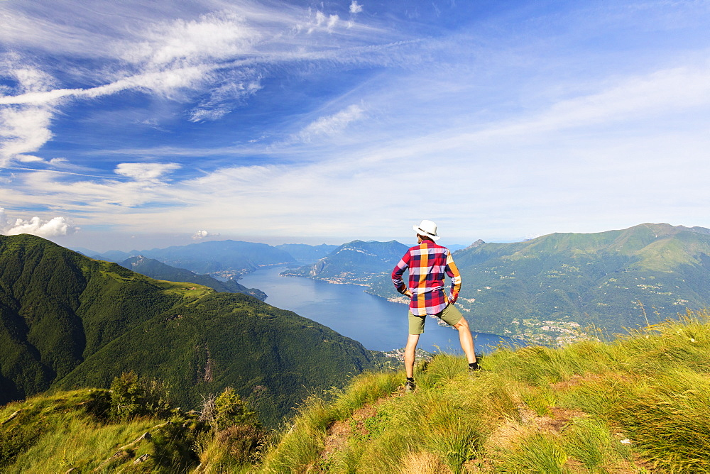 Hiker on Monte Legnoncino admires Lake Como, Lecco province, Lombardy, Italy, Europe