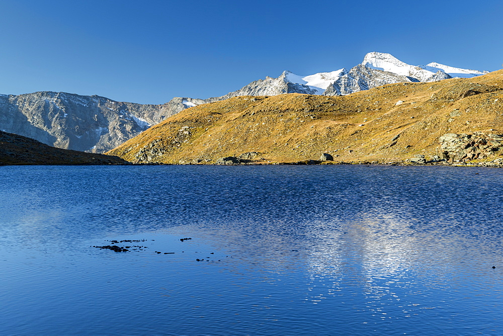 Sunrise and reflections on Aiguille Rousse, Gran Paradiso National Park, Alpi Graie (Graian Alps), Italy, Europe