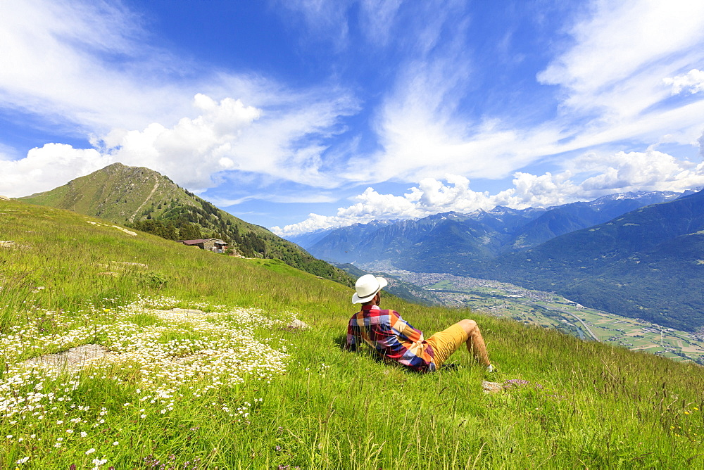 Man with hat relaxes on green meadows looking towards Morbegno, Alpe Bassetta, Valtellina, Sondrio, Lombardy, Italy, Europe