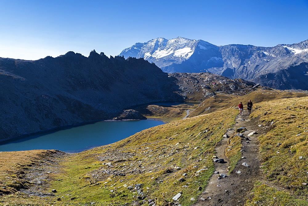 Hikers walking on the Colle del Nivolet beside Rossett Lake (Lago Rossett), Gran Paradiso National Park, Alpi Graie (Graian Alps), Italy, Europe