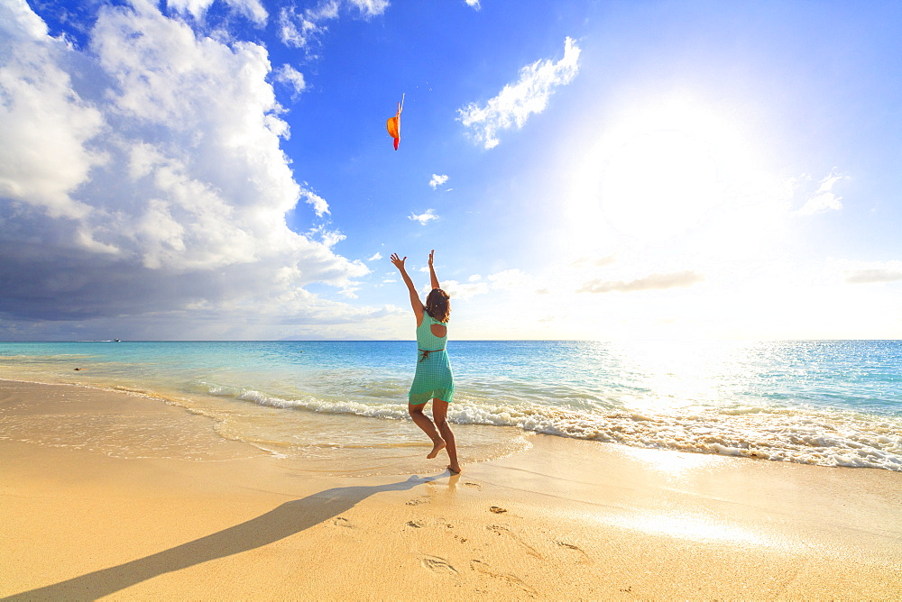 Woman on seashore throws the hat up in the air, Ffryes Beach, Antigua, Antigua and Barbuda, Leeward Islands, West Indies, Caribbean, Central America