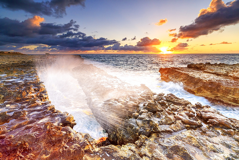 Waves crashing on cliffs at sunrise, Devil's Bridge, Antigua, Antigua and Barbuda, Leeward Islands, West Indies, Caribbean, Central America