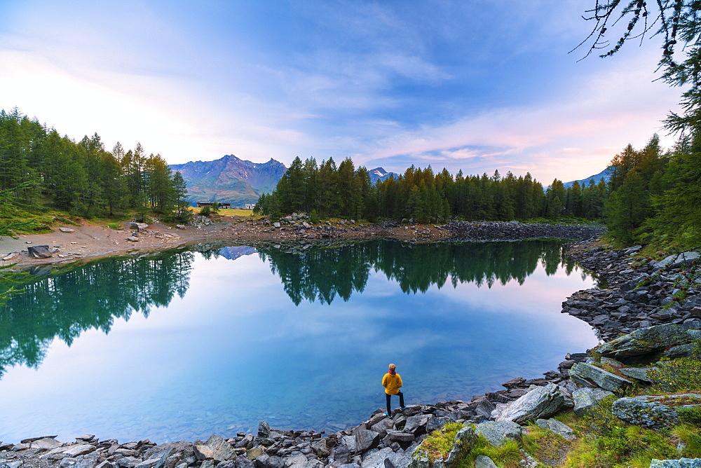 Hiker admires sunrise on lakeshore, Lago Azzurro, Spluga Valley, Sondrio province, Valtellina, Lombardy, Italy, Europe