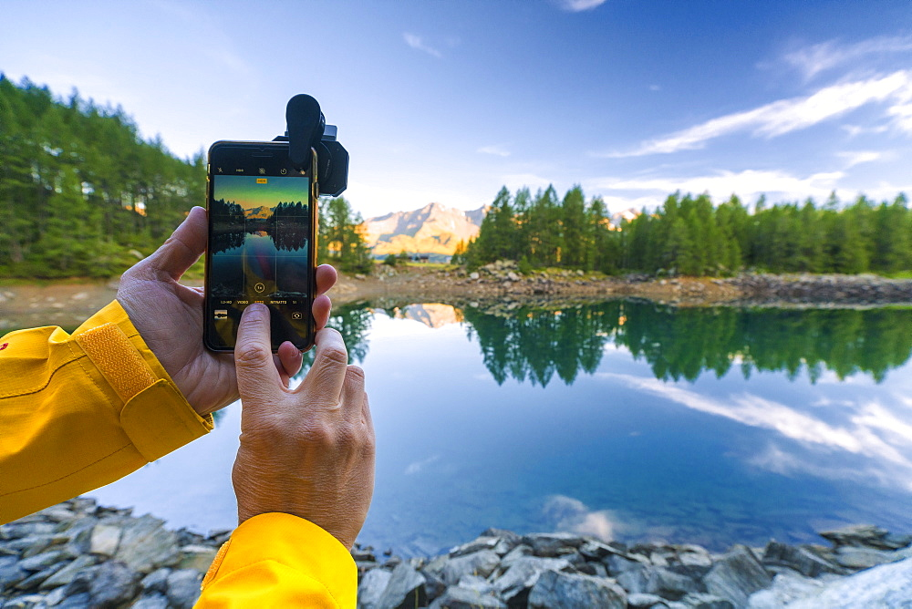 Hiker snaps photos with smartphone, Lago Azzurro, Spluga Valley, Sondrio province, Valtellina, Lombardy, Italy, Europe