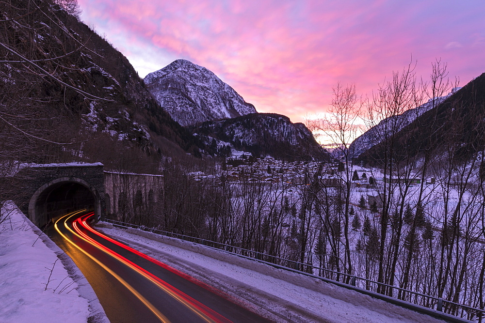 Car trail lights on the icy road at dawn, Campodolcino, Spluga valley, Sondrio province, Valtellina, Lombardy, Italy, Europe