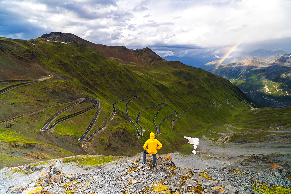 Man on rocks admires the rainbow on the winding road, Stelvio Pass, South Tyrol side, Valtellina, Lombardy, Italy, Europe