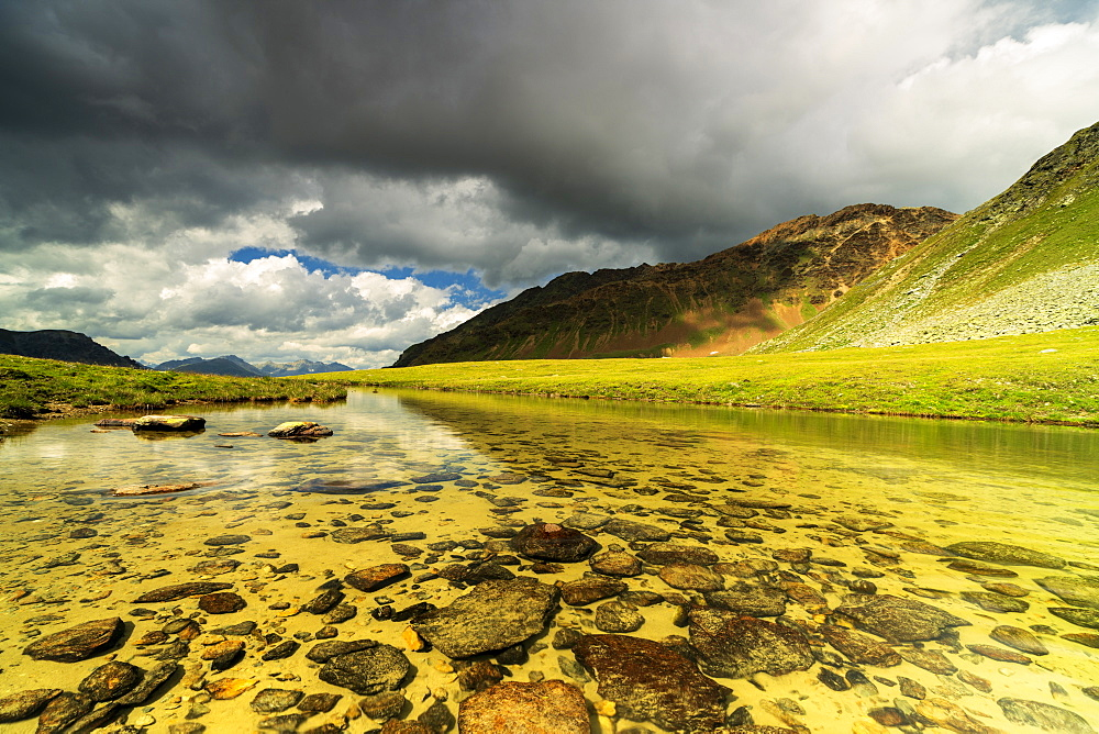 Storm clouds on Piz Umbrail reflected in the pristine alpine lake, Stelvio Pass, Braulio Valley, Valtellina, Lombardy, Italy