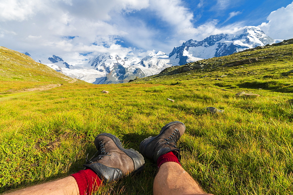 Hiker rests on grass looking towards Monte Rosa massif, Riffelalp, Zermatt, canton of Valais, Swiss Alps, Switzerland, Europe
