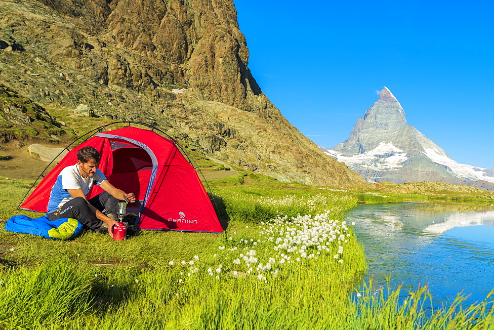 Hiker at lake Riffelsee makes coffee outside tent facing the Matterhorn, Zermatt, canton of Valais, Swiss Alps, Switzerland, Europe
