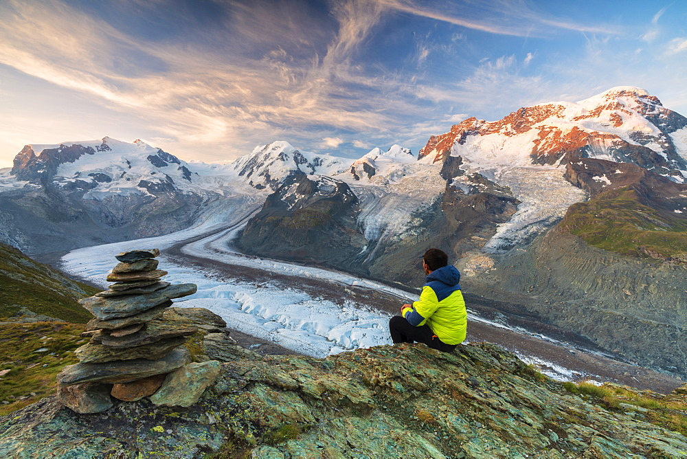 Hiker sitting on rocks looking towards Monte Rosa glacier, Zermatt, canton of Valais, Swiss Alps, Switzerland, Europe