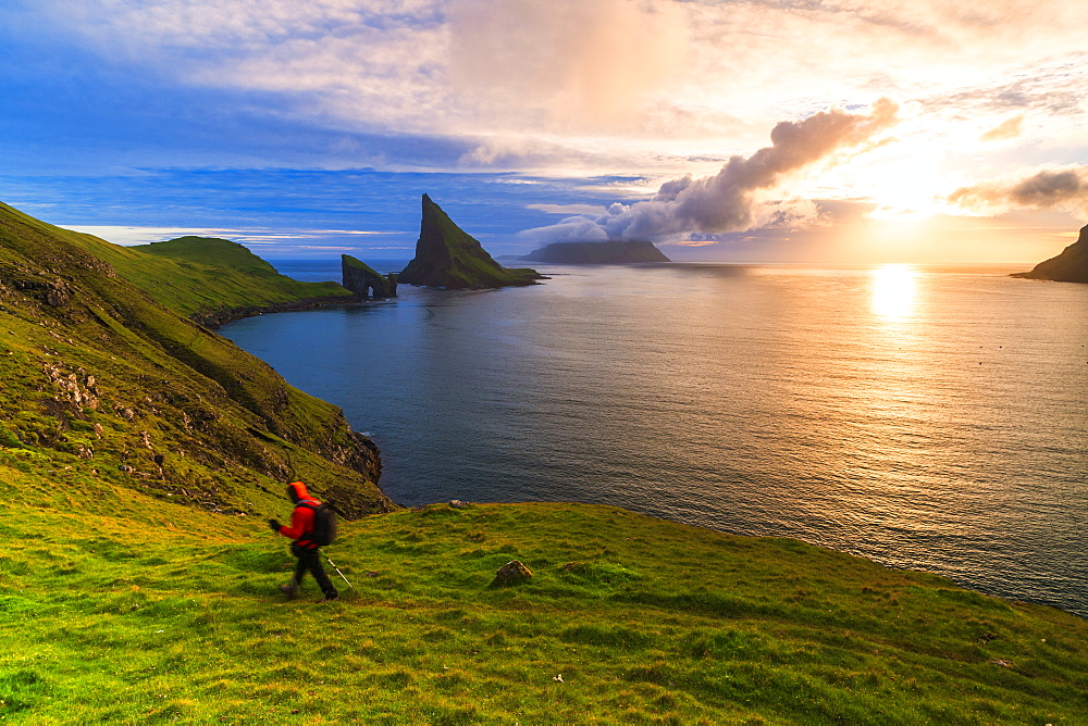 Trekker on the hiking trail to Drangarnir rock, Vagar island, Faroe Islands, Denmark, Europe