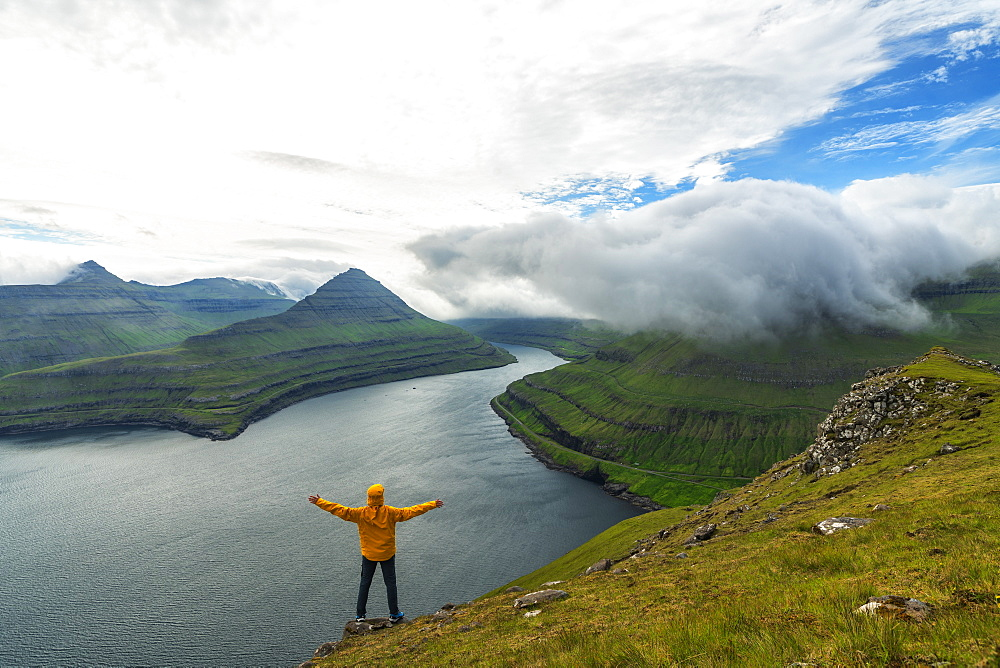 Man with open arms rejoices looking to the fjords, Funningur, Eysturoy island, Faroe Islands, Denmark - 1179-3637
