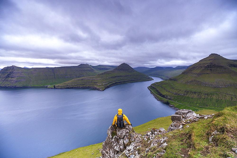 Hiker sitting on rocks looking at the fjords, Funningur, Eysturoy island, Faroe Islands, Denmark, Europe
