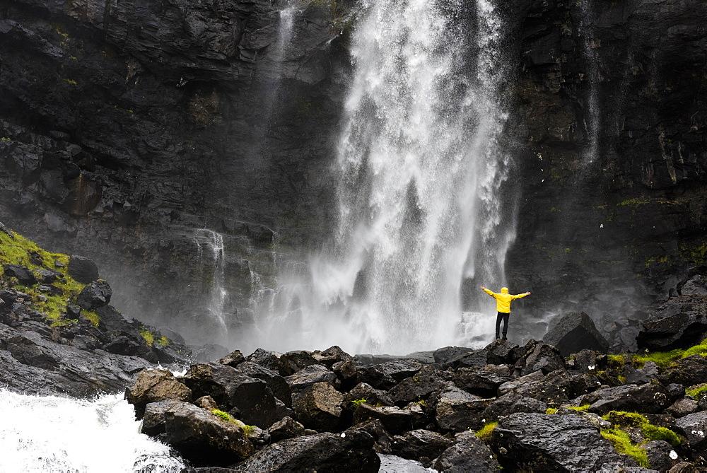 Hiker at Fossa waterfall, Streymoy island, Faroe Islands, Denmark, Europe