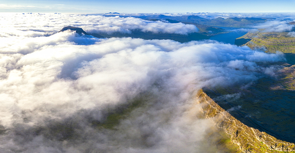 Aerial panoramic of clouds on the rocky peaks of Skælingsfjall and Sornfelli mountains, Streymoy island, Faroe Islands, Denmark