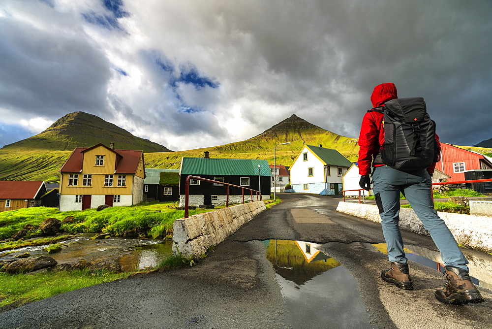 Hiker in the traditional village of Gjogv, Eysturoy island, Faroe Islands, Denmark, Europe