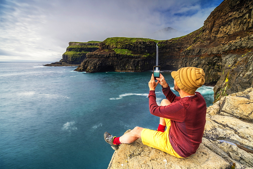 Man with smartphone snaps photos at Gasadalur waterfall, Vagar island, Faroe Islands, Denmark - 1179-3677