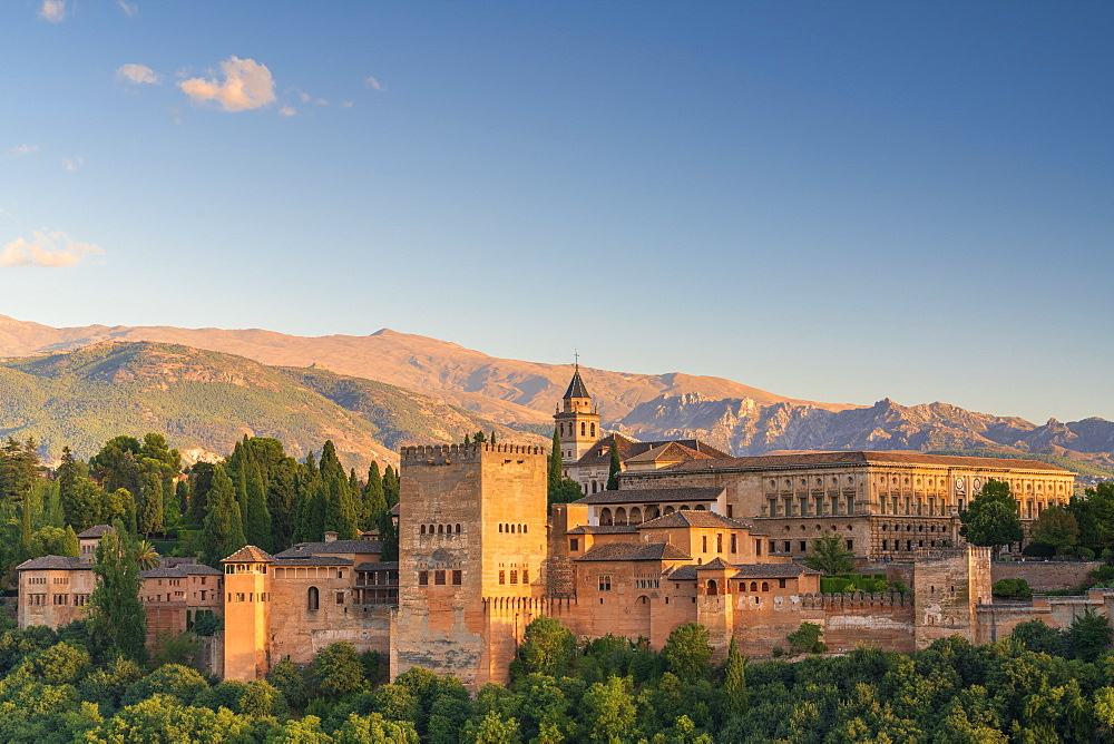 The Alhambra palace and fortress complex surrounded by woods and Sierra Nevada at sunset, Granada, Andalusia, Spain