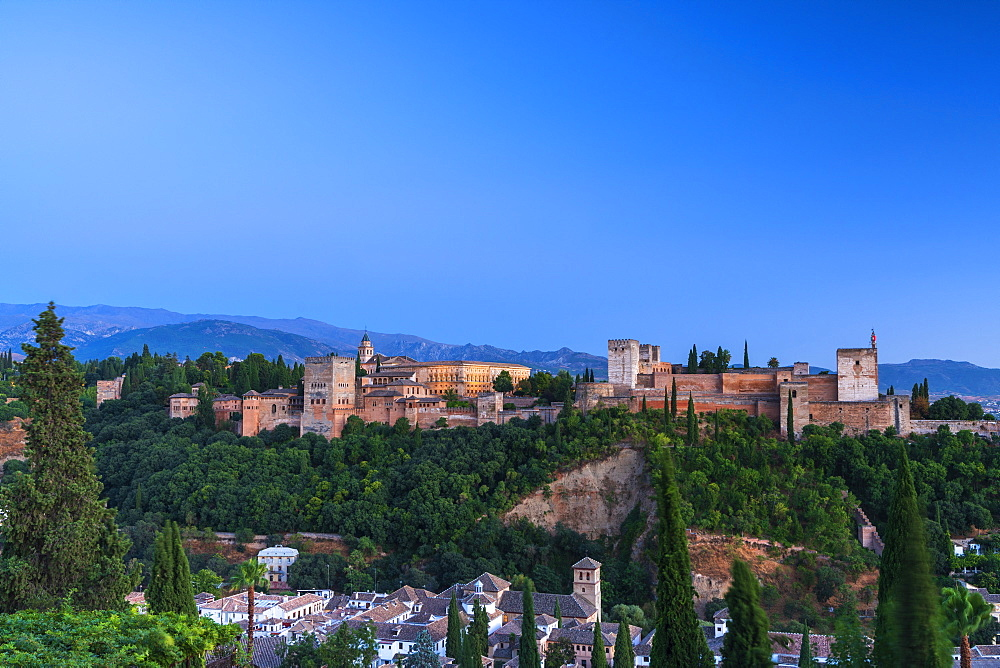 Alhambra palace and fortress complex surrounded by woods and Sierra Nevada mountain range, Granada, Andalusia, Spain