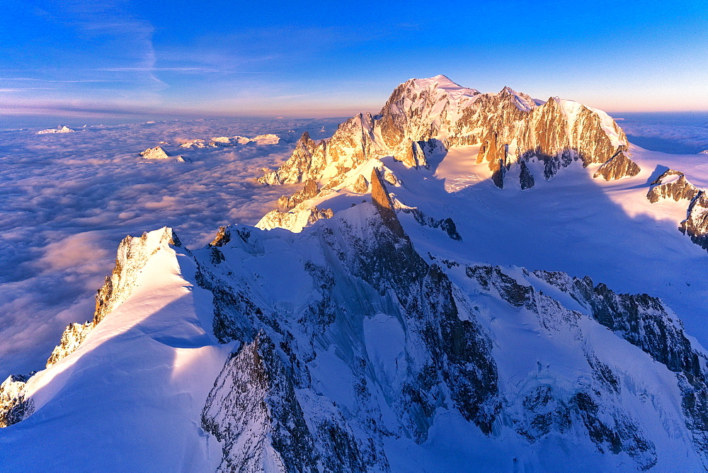 Aerial view of snowy peaks of Mont Blanc and Dent du Geant during sunrise, Courmayeur, Aosta Valley, Italy, Europe