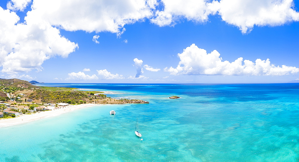 Aerial panoramic by drone of boats in the blue Caribbean Sea approaching to Turners Beach, Antigua, Antigua and Barbuda, Leeward Islands, West Indies, Caribbean, Central America