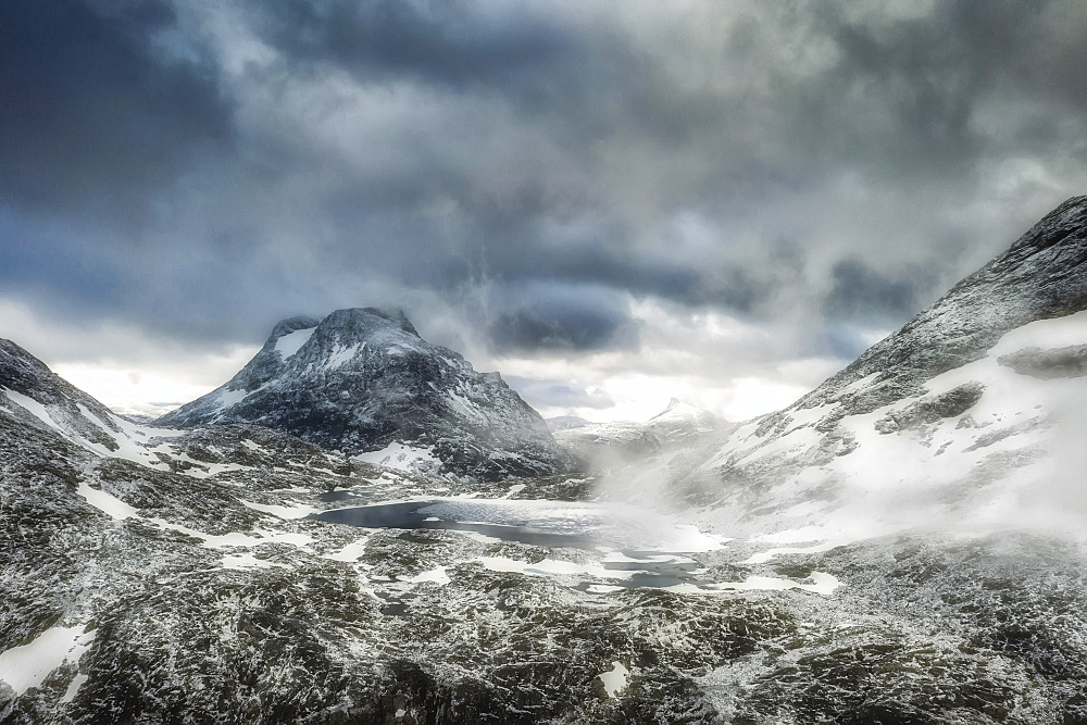 Storm clouds over Olaskarsvatnet lake at feet of the snowcapped Olaskarstind mountain, Venjesdalen valley, Andalsnes, Norway, Scandinavia, Europe