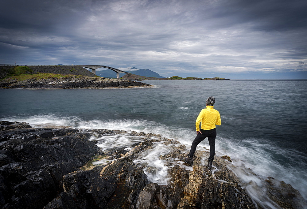 Hiker admiring the Atlantic Road from cliffs washed by waves, More og Romsdal county, Norway, Scandinavia, Europe