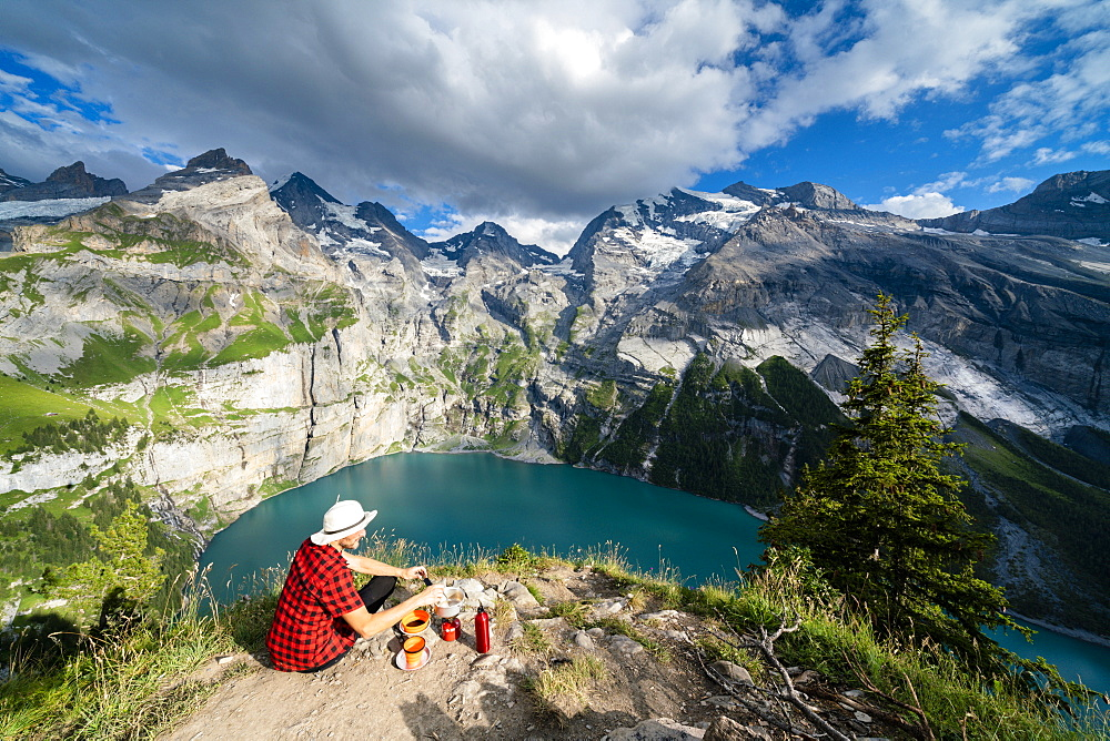 Hiker cooking food on camping stove high up above Oeschinensee lake, Bernese Oberland, Kandersteg, Canton of Bern, Switzerland, Europe