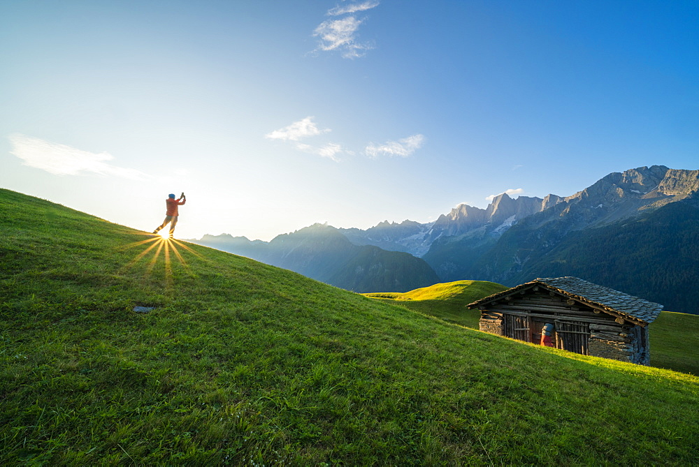 Man lit by the sunburst photographing Piz Badile and Cengalo, Tombal, Soglio, Val Bregaglia, canton of Graubunden, Switzerland, Europe