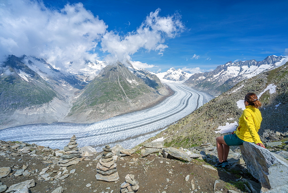 Side view of woman sitting on rocks admiring Aletsch Glacier from Eggishorn viewpoint, Bernese Alps, canton Valais, Switzerland, Europe