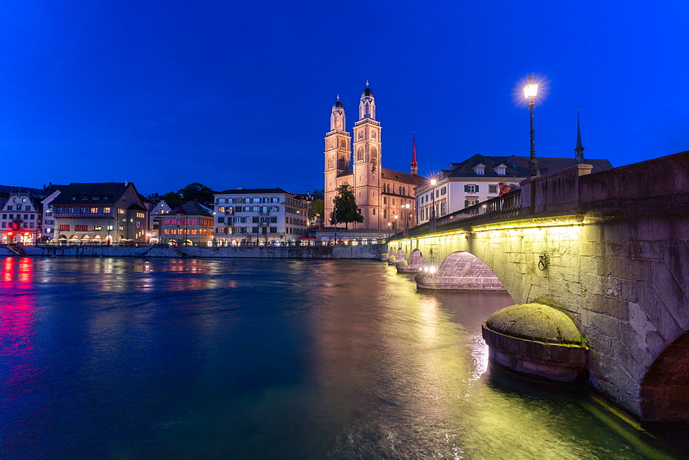 Illuminated buildings of Limmatquai and Grossmunster at dusk from Munsterbrucke bridge, Zurich, Switzerland, Europe